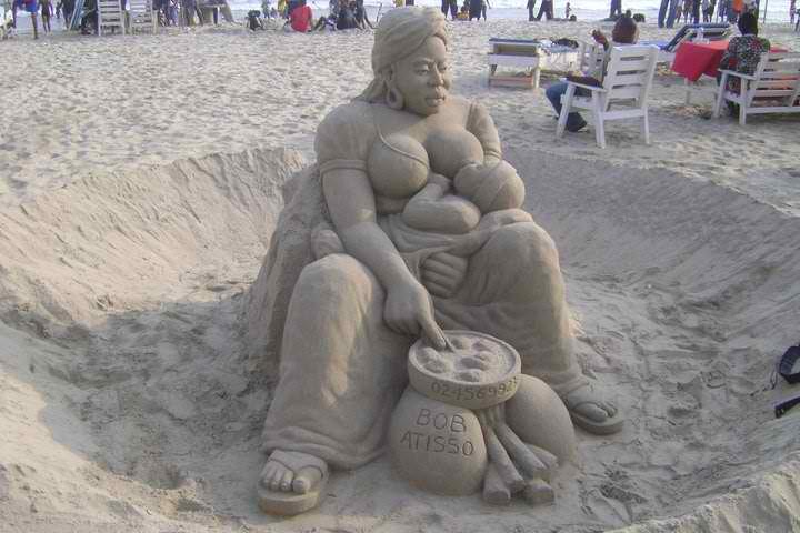 Photo d'une sculpture de sable réalisée par Bob Atisso : maman et bébé en plein allaitement maternel